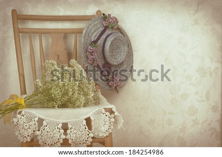 Vintage Still Life of an Old Hat for a Woman with wooden chair, white flowers, and lace against flowery wallpaper.  An invite for a party, tea, Mothers Day brunch, Easter dinner.   - stock photo