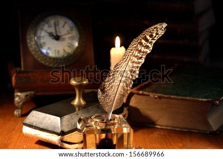 Vintage still life. Old inkstand near lighting candle and clock - stock photo
