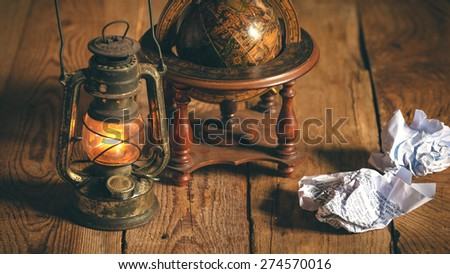 Vintage still life stuff on a rustic wooden table,retro camera, glasses, pencil, pen, old rusty kerosene lamp. - stock photo