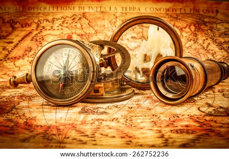 Vintage still life. Vintage magnifying glass and compass lies on an ancient world map in 1565. - stock photo