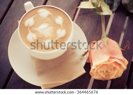 Vintage Still Life with Coffee cup, artistic cream decoration with artificial roses.