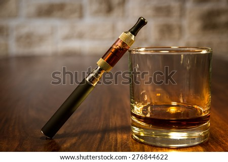 vintage still life with electronic cigarette and a glass of rum - stock photo