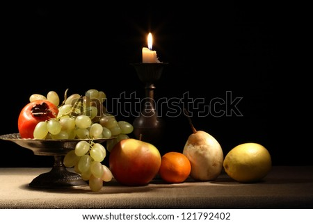 Vintage still life with fruits in bowl near lighting candle - stock photo