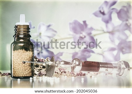vintage still life with homeopathy globule, syringe with blood, some spices and flowers. - stock photo