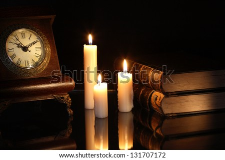 Vintage still life with old books and clock near lighting candles