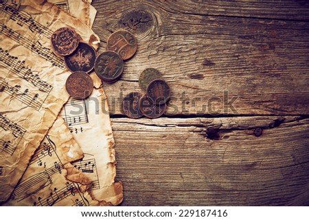 Vintage still life with old coins and music sheets on wooden background - stock photo