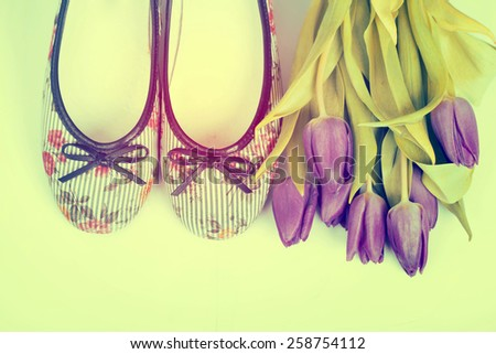 Vintage still life with purple tulips and retro styled shoes - stock photo