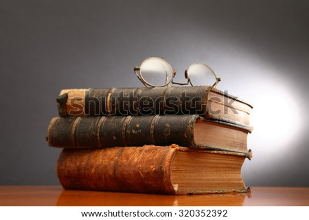 Vintage still life with spectacles on stack of old books on dark background - stock photo