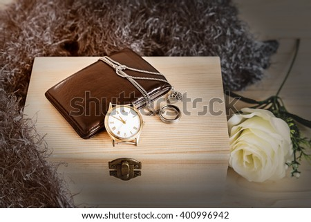 Vintage still life with watch and wallet and ring on a wooden box - stock photo