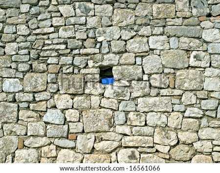 Vintage stone wall where one brick missing. - stock photo