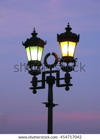 Vintage street lamp glowing green and yellow light on background of sky on sunset - stock photo