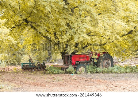 vintage style.a red tractor under big tree - stock photo