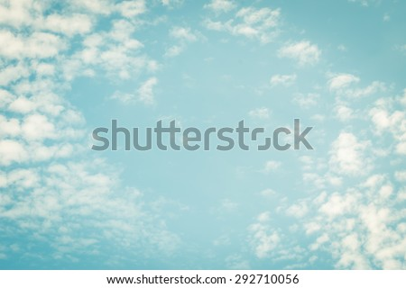 Vintage style blurred nature background of blue sky and soft scattered clouds with heart shaped empty space in the air in the middle : Holiday lovely blur puffy clouds with summer sky in retro style   - stock photo