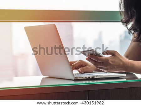 Vintage style city lifestyle woman hands working on computer typing laptop keyboard using IOT IT SEO 4G wifi cyber internet online digital media technology pc device in urban office space environment  - stock photo