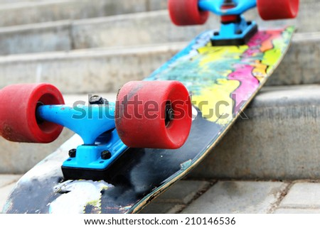 Vintage Style Colorful Skateboard with Red Wheels on a Street Stairs - stock photo