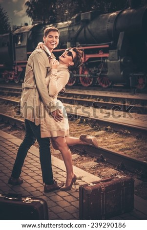 Vintage style couple with suitcases on train station platform - stock photo