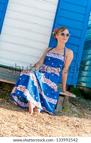 Vintage style girl in sun dress and retro sunglasses relaxing in front of a beach hut - stock photo