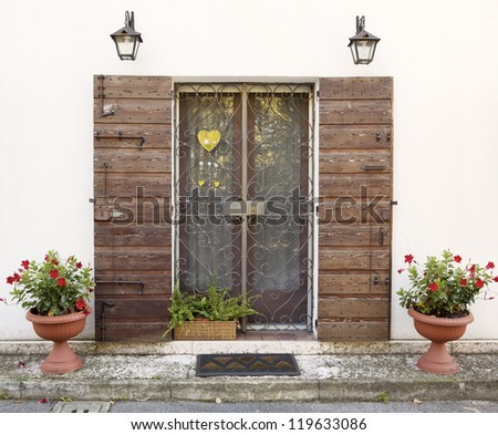 Vintage style house entrance (white walls and wooden door, decorated with flowerpots)