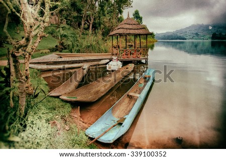 Vintage style image of traditional boats at Lake Bunyonyi in Uganda, Africa, at the borders of Uganda, Congo and Rwanda, not far from the Bwindi National Park, home of the last mountain gorillas - stock photo