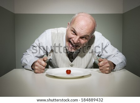 Vintage style insane man having a sad dinner alone. - stock photo