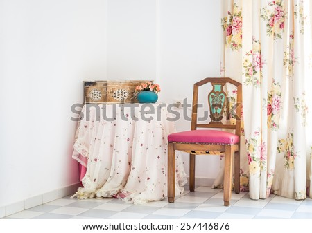 Vintage style interior with table, carved chair and floral curtain  - stock photo