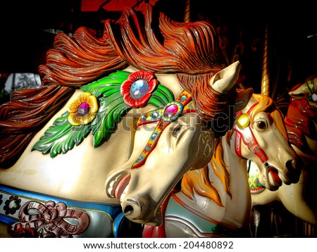 Vintage style nostalgic carousel riding horse carved head on an old fashioned merry go round ride at the fairground amusement park - stock photo