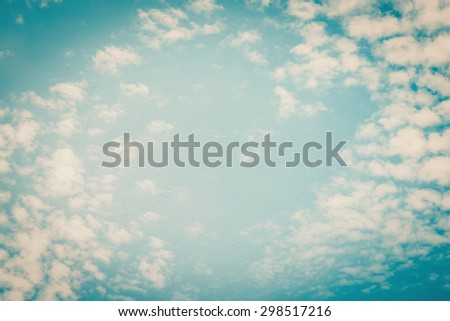 Vintage style paper texture with blurred nature background of blue sky and soft scattered clouds with heart shaped empty space in the air in the middle: Water colour  textured paper with retro sky    - stock photo