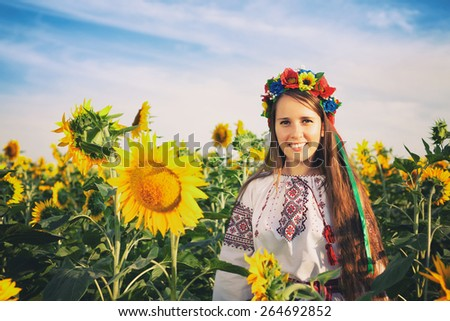 Vintage style photo of beautiful young woman at sunflower field - stock photo
