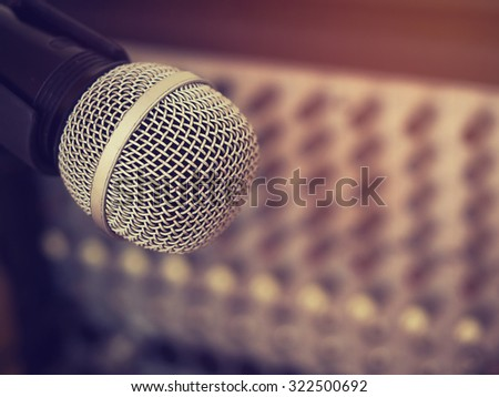 Vintage style photo of the microphone in a recording studio or concert hall with amplifier equipment in out of focus background. : Filtered process.