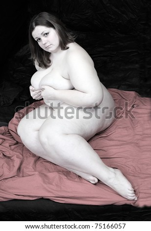 Vintage style picture of a overweight woman on a pink blanket. Black background. - stock photo