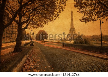 vintage style picture of Paris at dusk with a street along the Seine and the Eiffel Tower in the background - stock photo