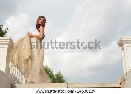 vintage style portrait of the beautiful girl in white-golden gown on background cloudy sky