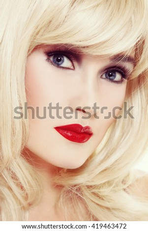 Vintage style portrait of young beautiful blonde woman with red lipstick