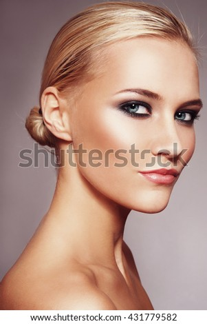Vintage style portrait of young beautiful blonde woman with smoky eyes - stock photo