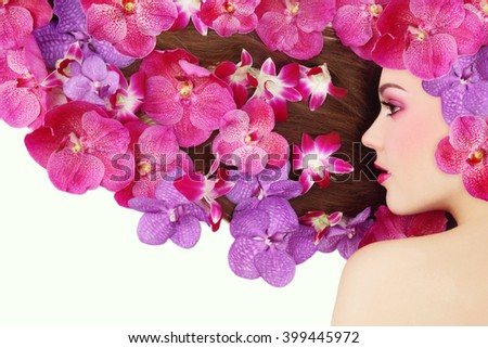 Vintage style profile portrait of young beautiful girl with bright make-up and colorful orchids in her long hair