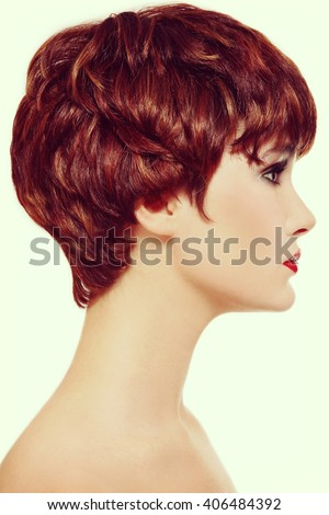 Vintage style profile portrait of young beautiful redhead woman with short haircut - stock photo