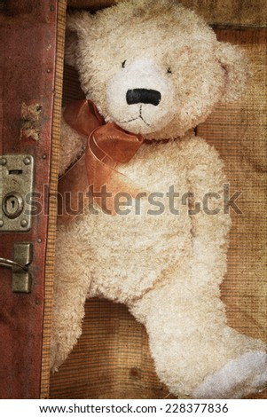 Vintage-style teddy bear and old suitcase - stock photo
