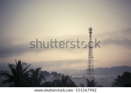 Vintage style telecom tower in the morning mist - stock photo