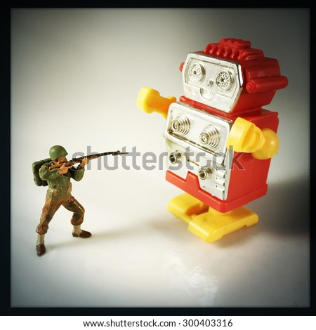 Vintage style Toy Soldier shooting at robot with an Instagram style filter - stock photo