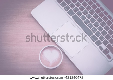 Vintage style with vignette filter of top view notebook (laptop) with coffee latte art heart on workspace of wooden table. Concept for workplace, freelance, blogger, social, programmer, background,