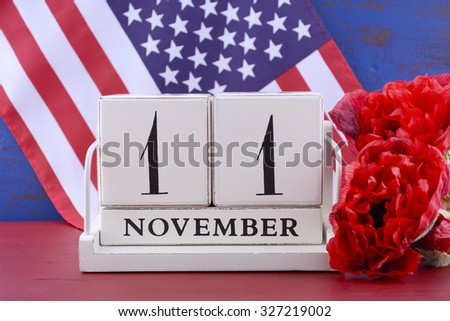 Vintage style wood block calendar for November 11, USA Veterans Day, with Stars and Stripes flag  and red Flanders poppy flowers for remembrance on red and blue wood background.  - stock photo
