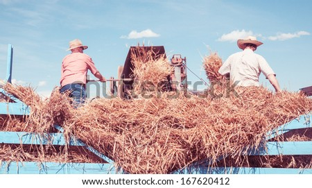 vintage styled image of farmers working - stock photo