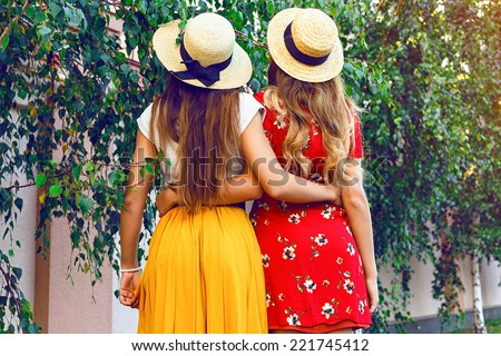 Vintage styled outdoor lifestyle fashion image of two pretty girls guys at city park, wearing retro hipster elegant dresses and straw hats. Bright instagram colors. - stock photo