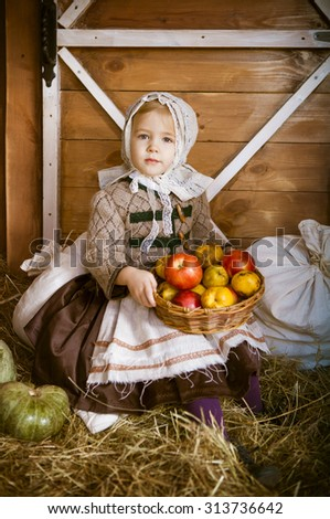 Vintage styled photo of little smiling girl in farm holding basket with apples - stock photo