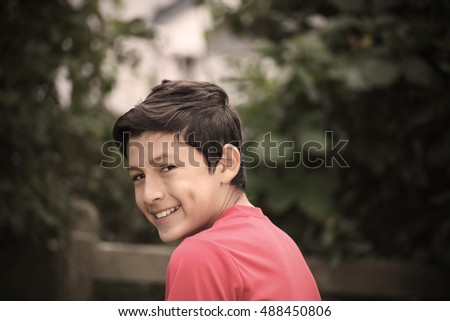 Vintage stylistic portrait of smiling boy with de-saturated look and vignetting - shot with vintage lens