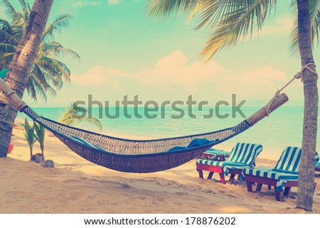 Vintage stylized hammock under palms trees on sunny tropical beach - stock photo