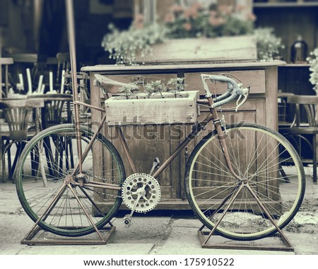 Vintage stylized photo of old bicycle carrying flowers - stock photo