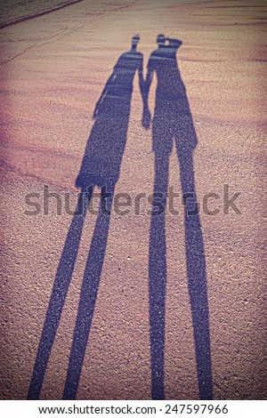 Vintage stylized picture of couple's shadow on beach. - stock photo
