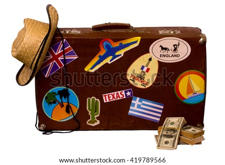 Vintage suitcase for travel with stickers of the countries visited, straw hat and dollars