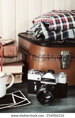 Vintage suitcase with clothes and books on wooden background - stock photo